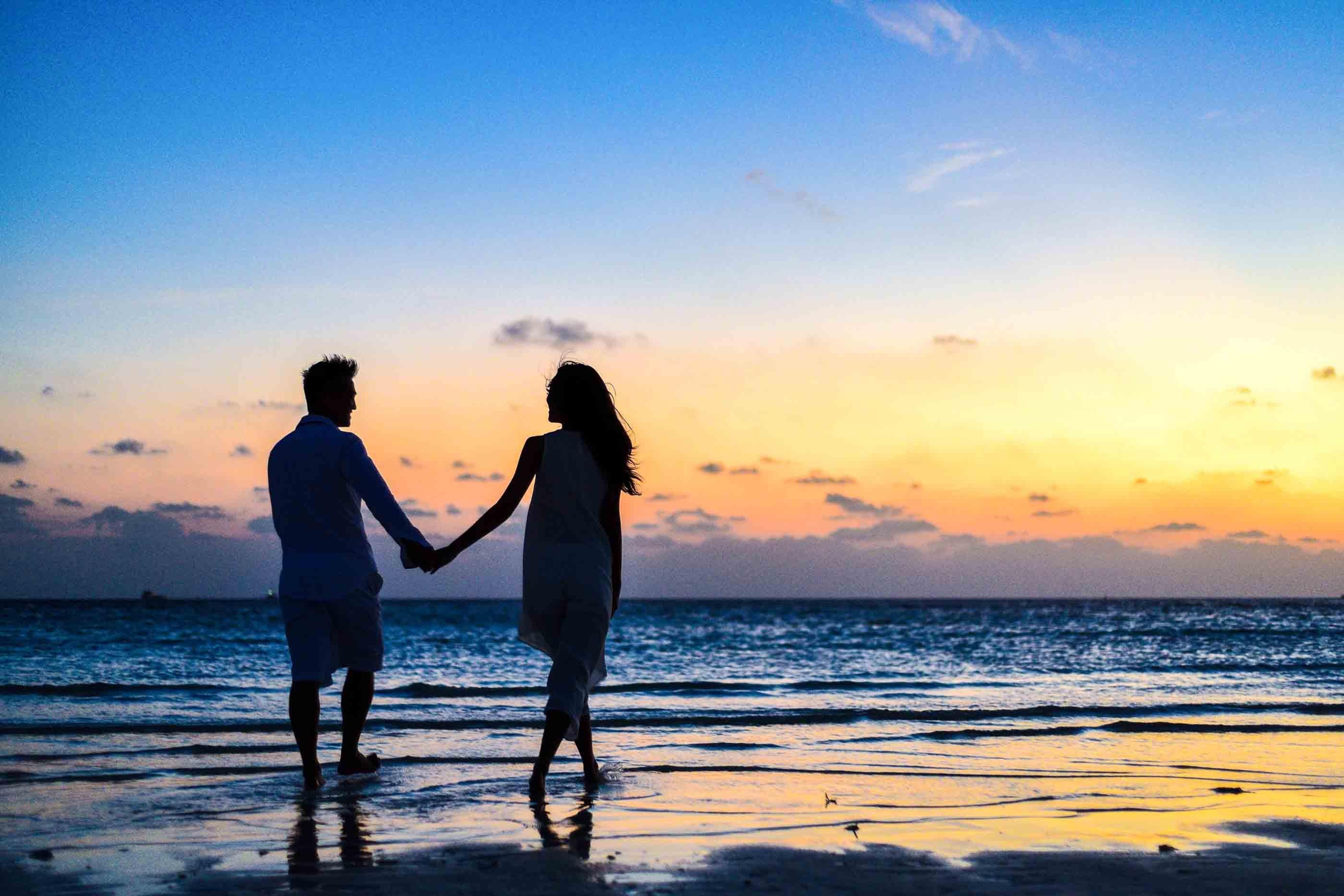 a couple near the beach during sunset