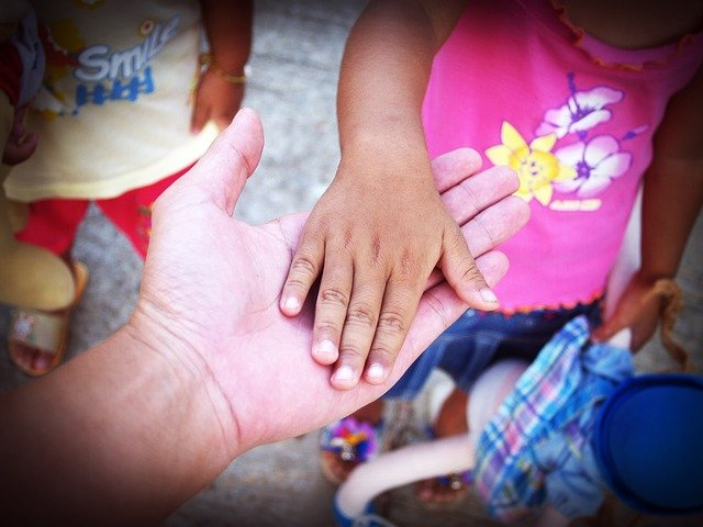 a child putting his hand in elders hand