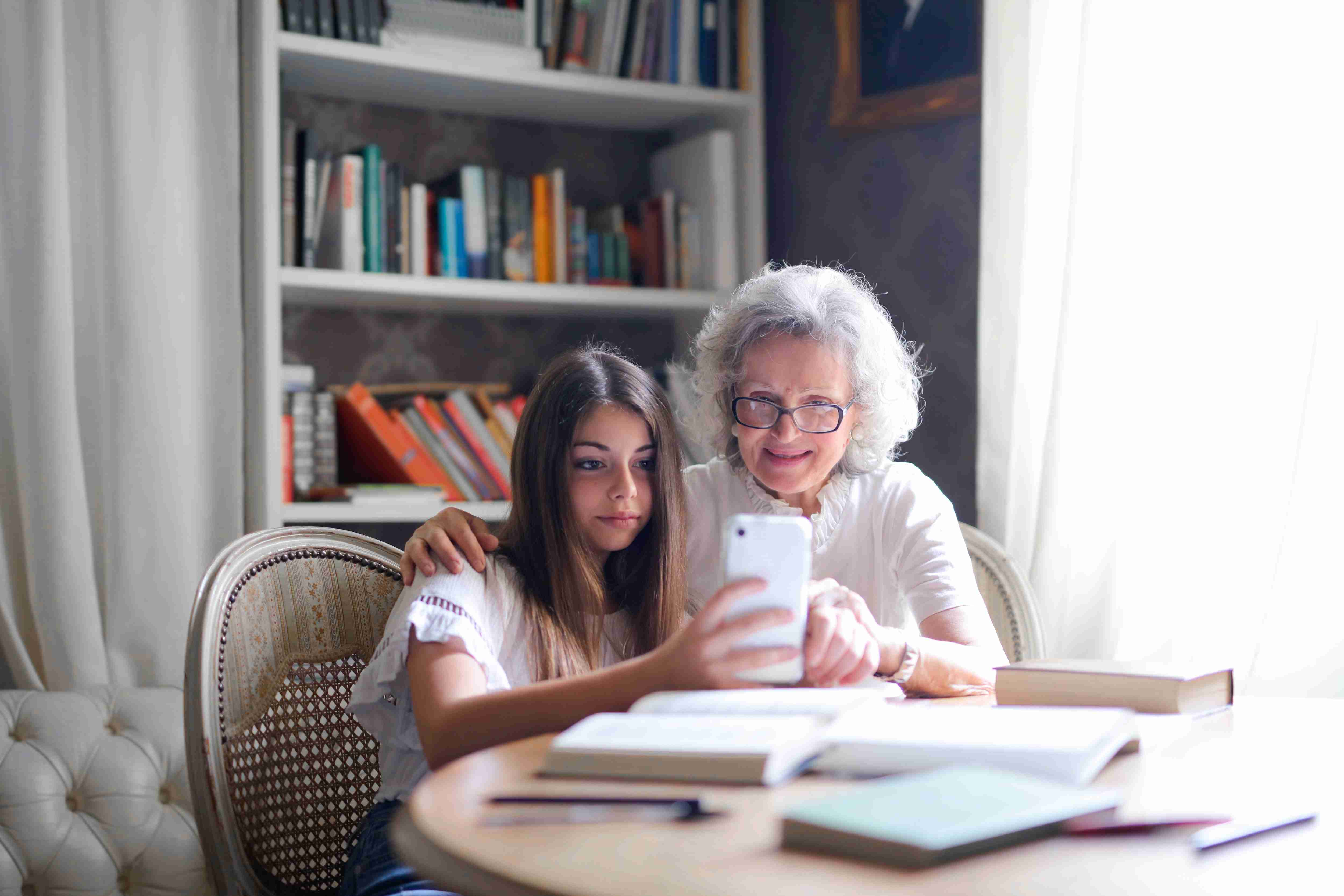 a young girl using social media and her grandmother is teaching her