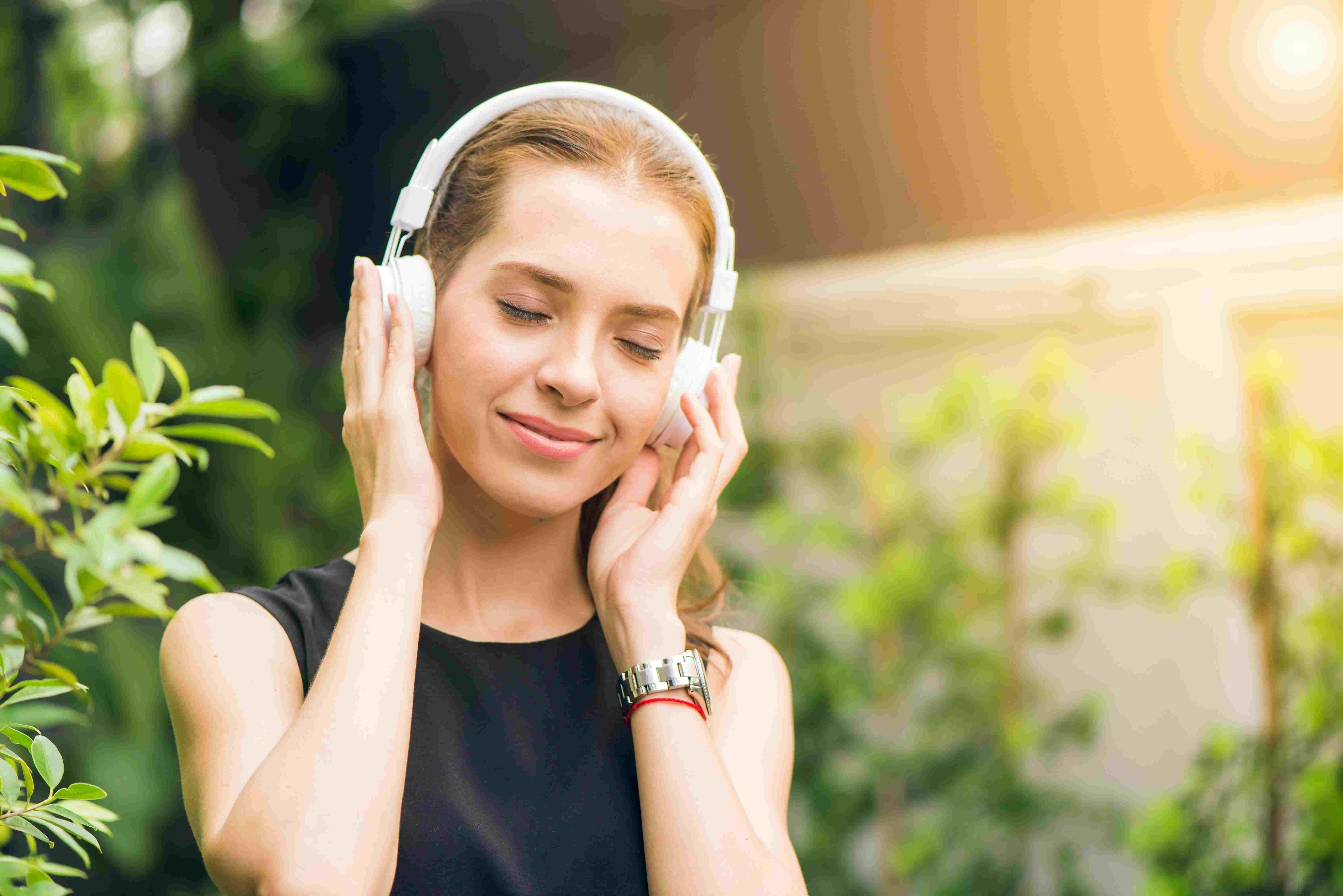 A GIRL LISTENING USIC IN WHITE HEADPHONES