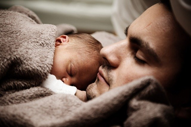 A baby sleeping on the chest of his father