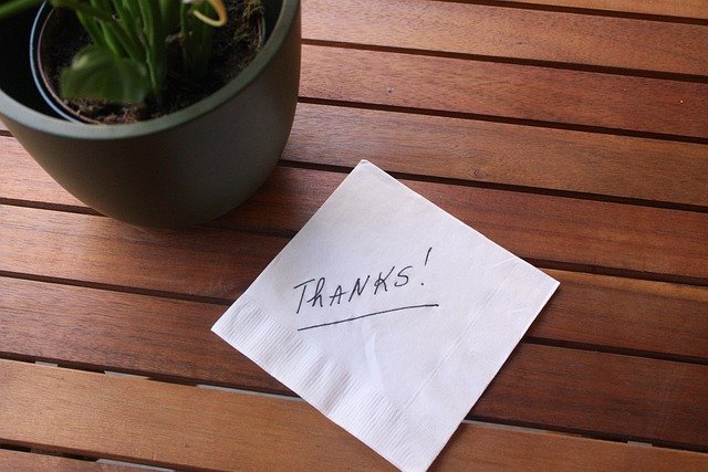 Thanks wrote by someone on a white note placed on a table