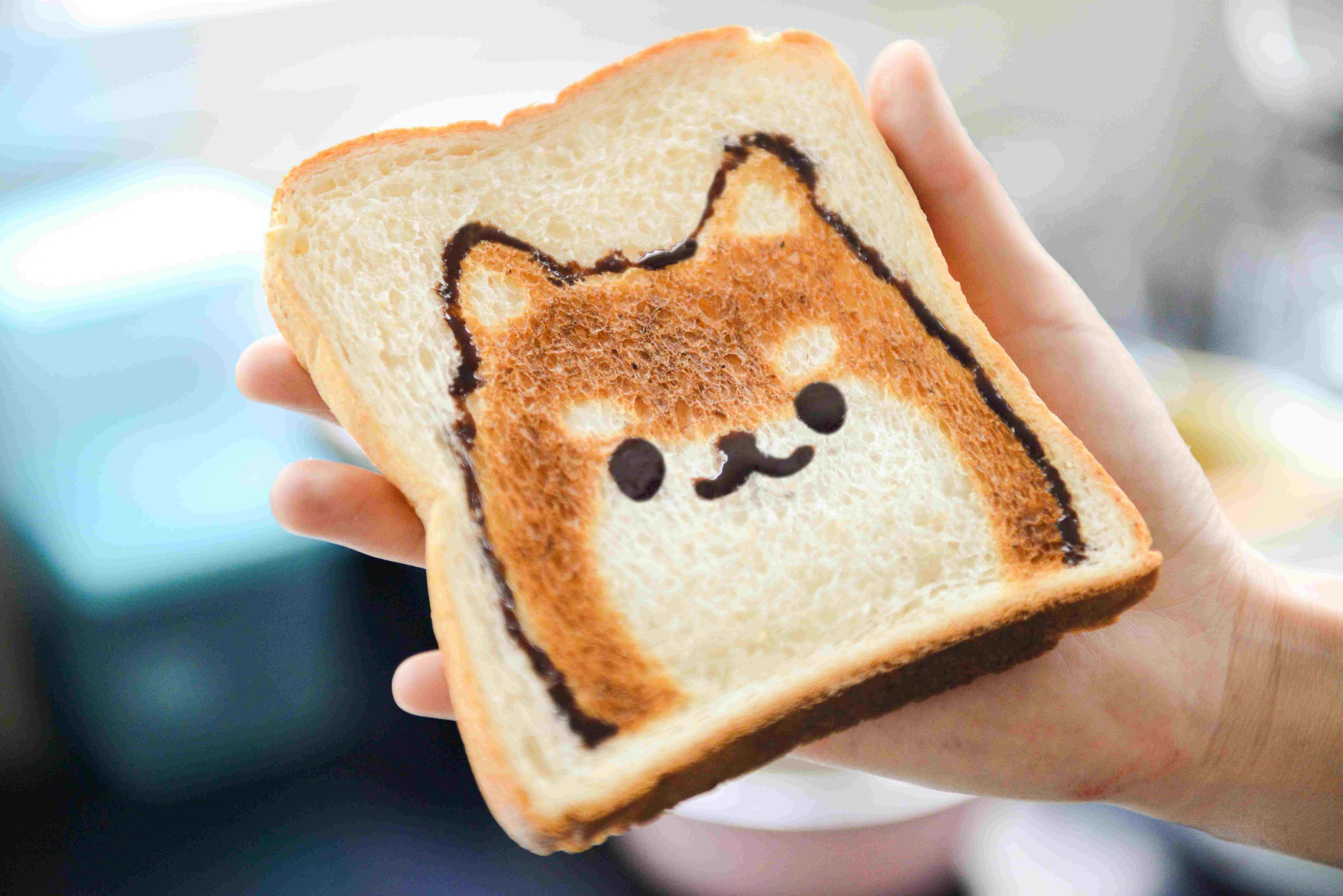 A child holding a bread with a cat face drawing on it