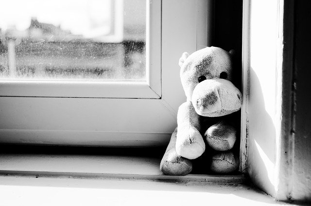 a small doll in window -black and white photo