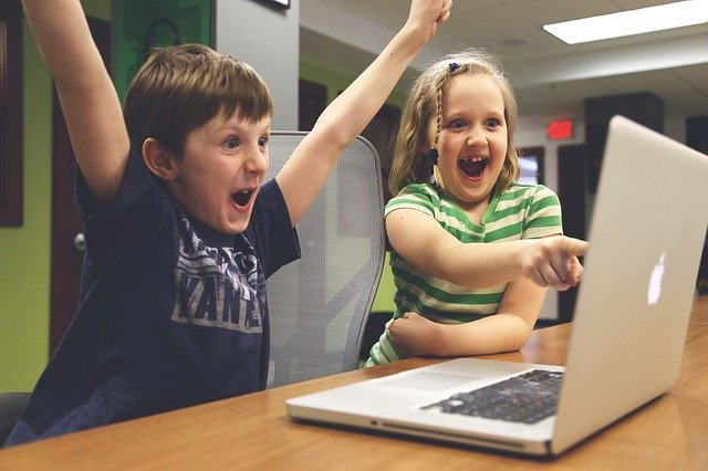 2 kids shouting and looking on macbook screen