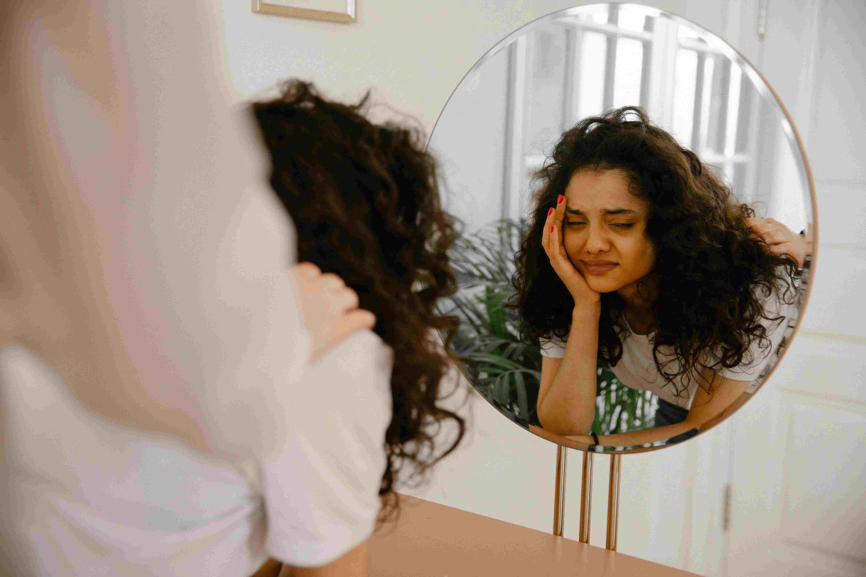 a depressed women watching in mirror