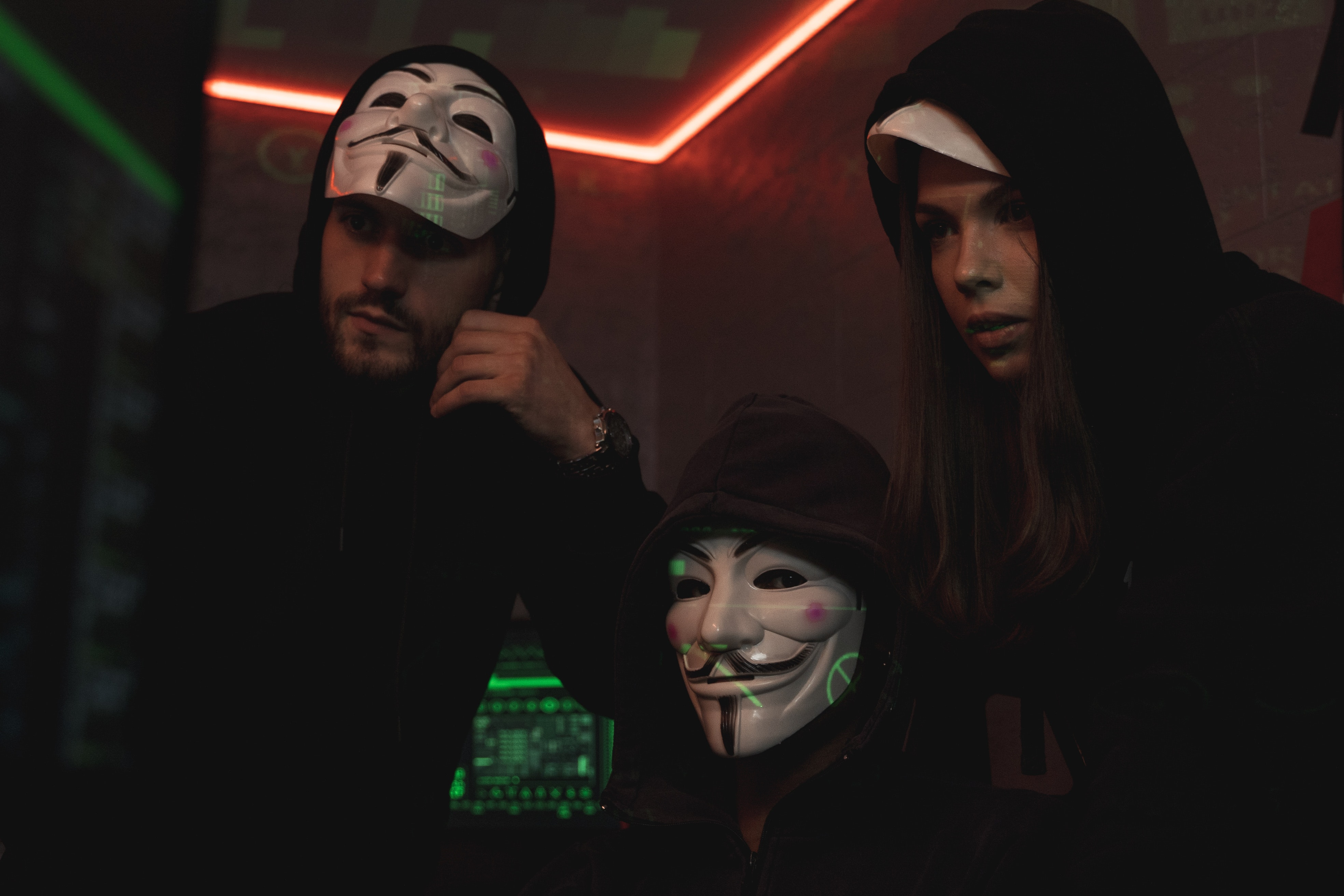 3 hackers wearning black hussies and masks looking at the kali linux machine screen
