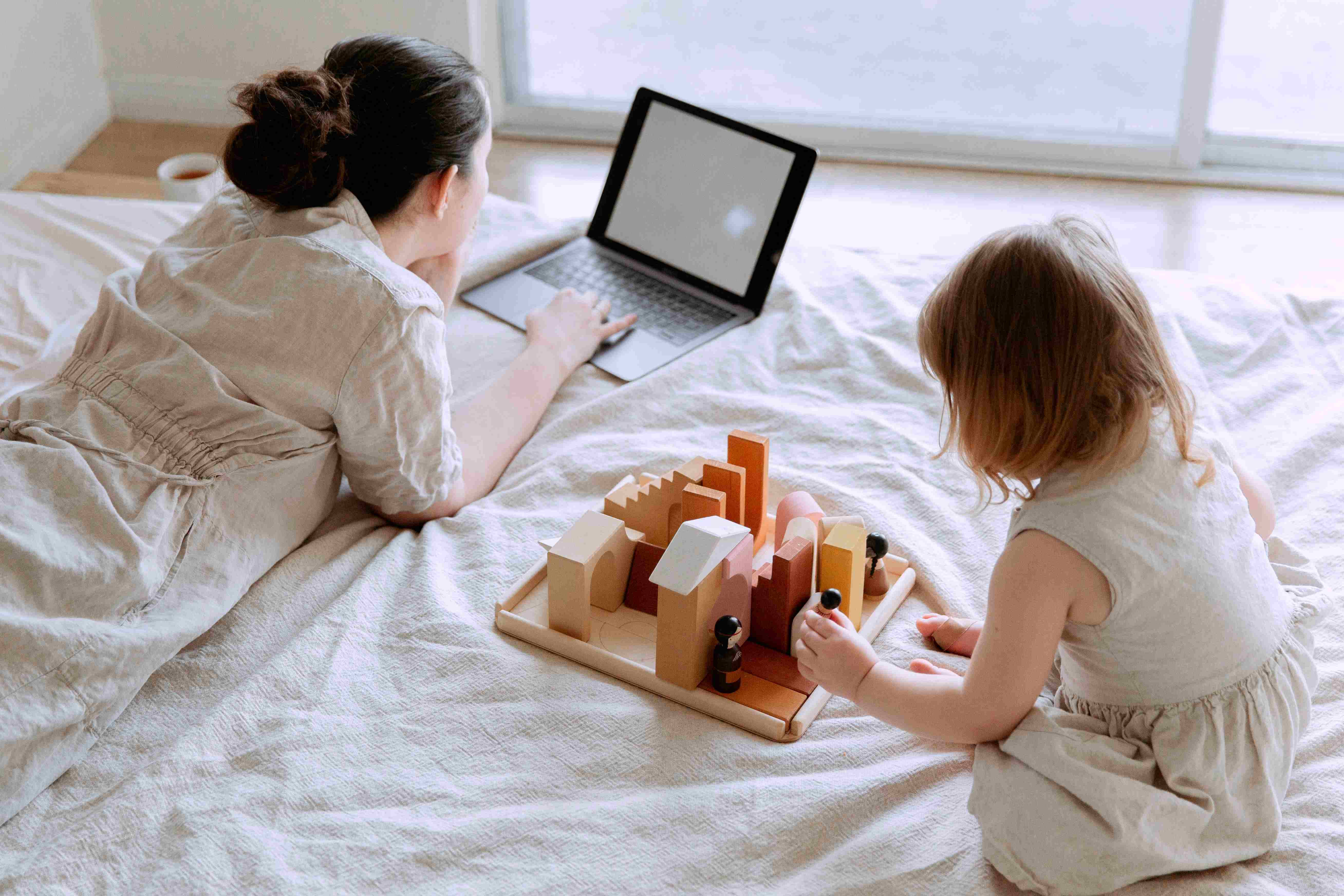 a mother doing office work while her daughter is playing alone
