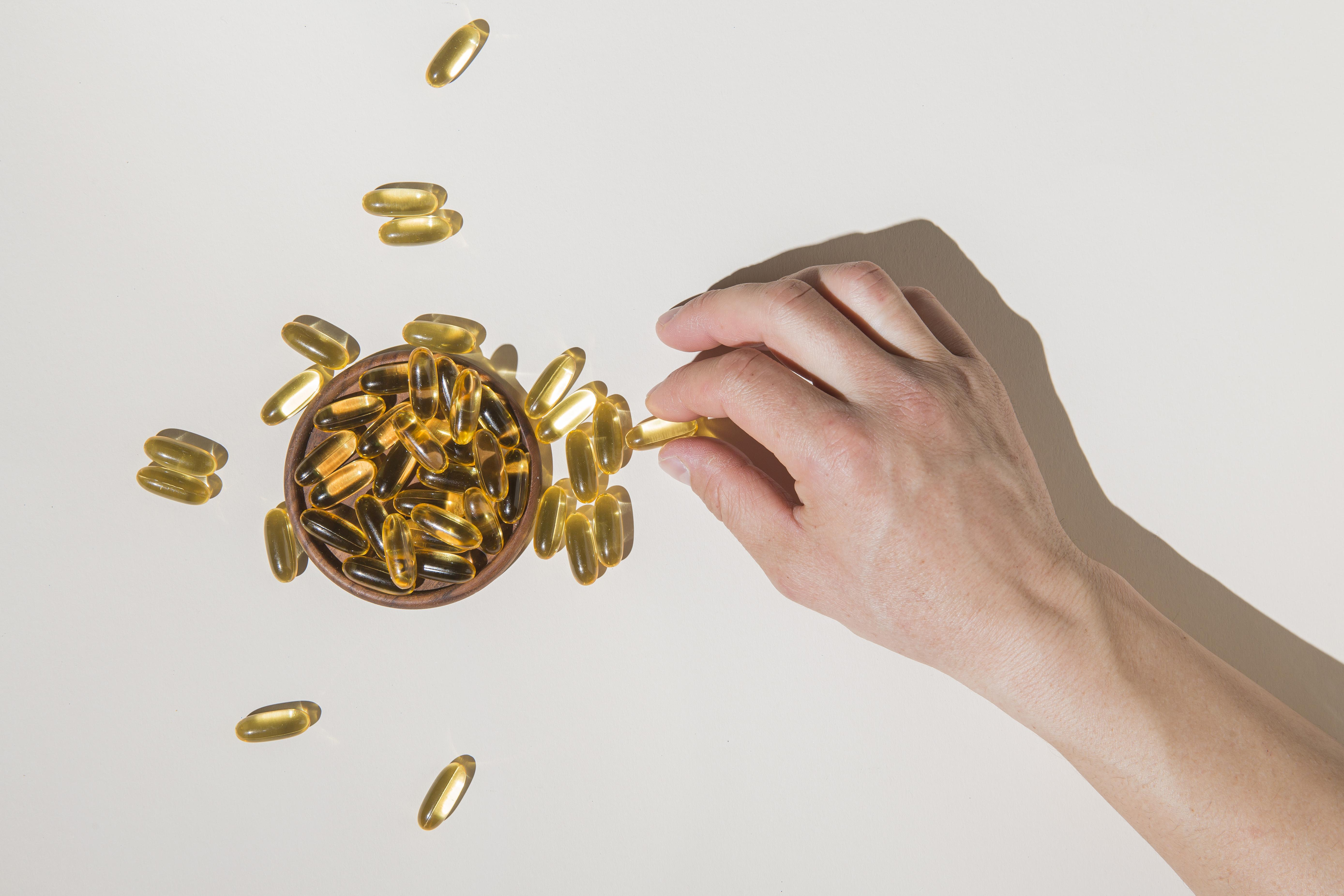 A man touching omega 3 capsule with hands
