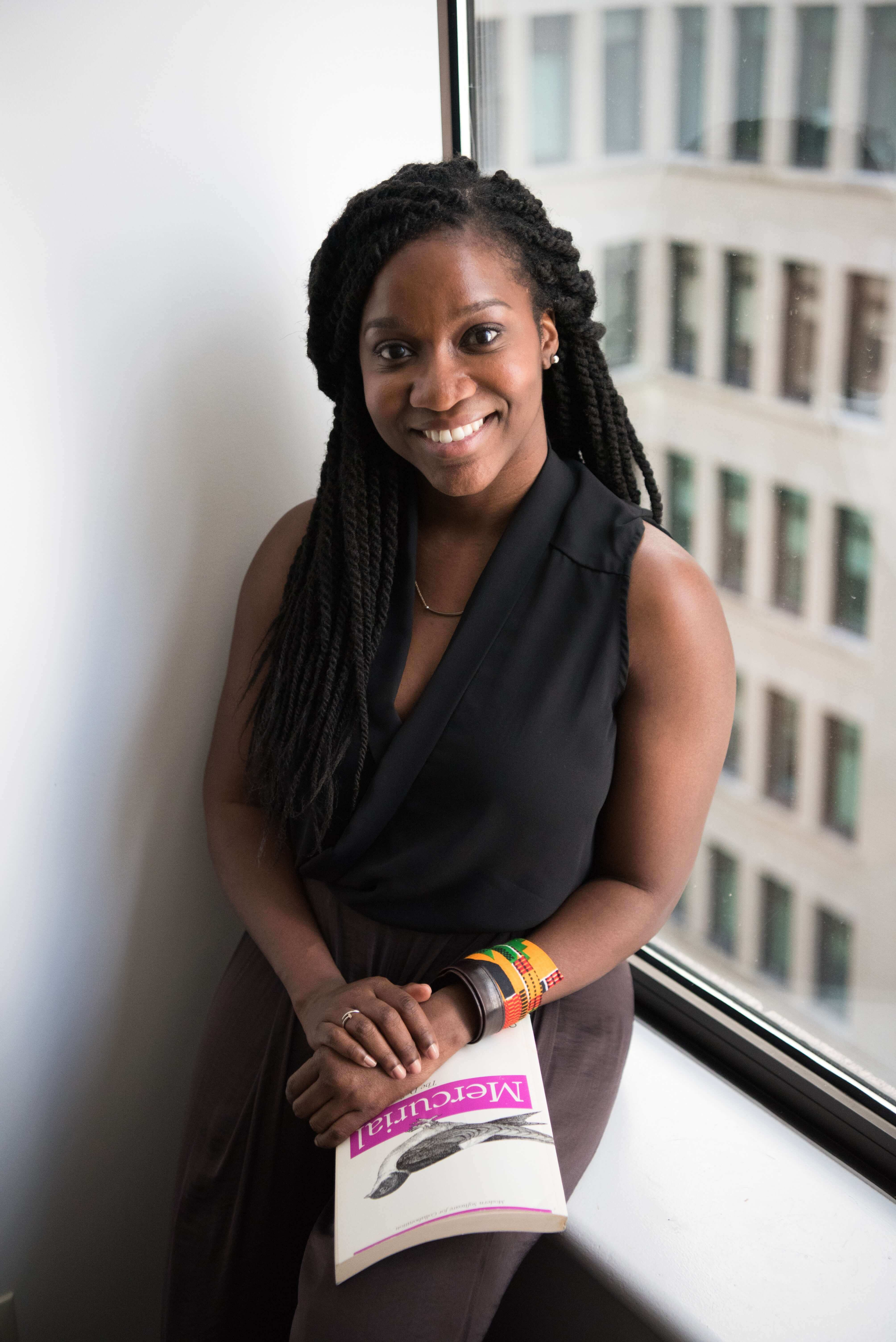 a smiling black women sitting in the window with the book