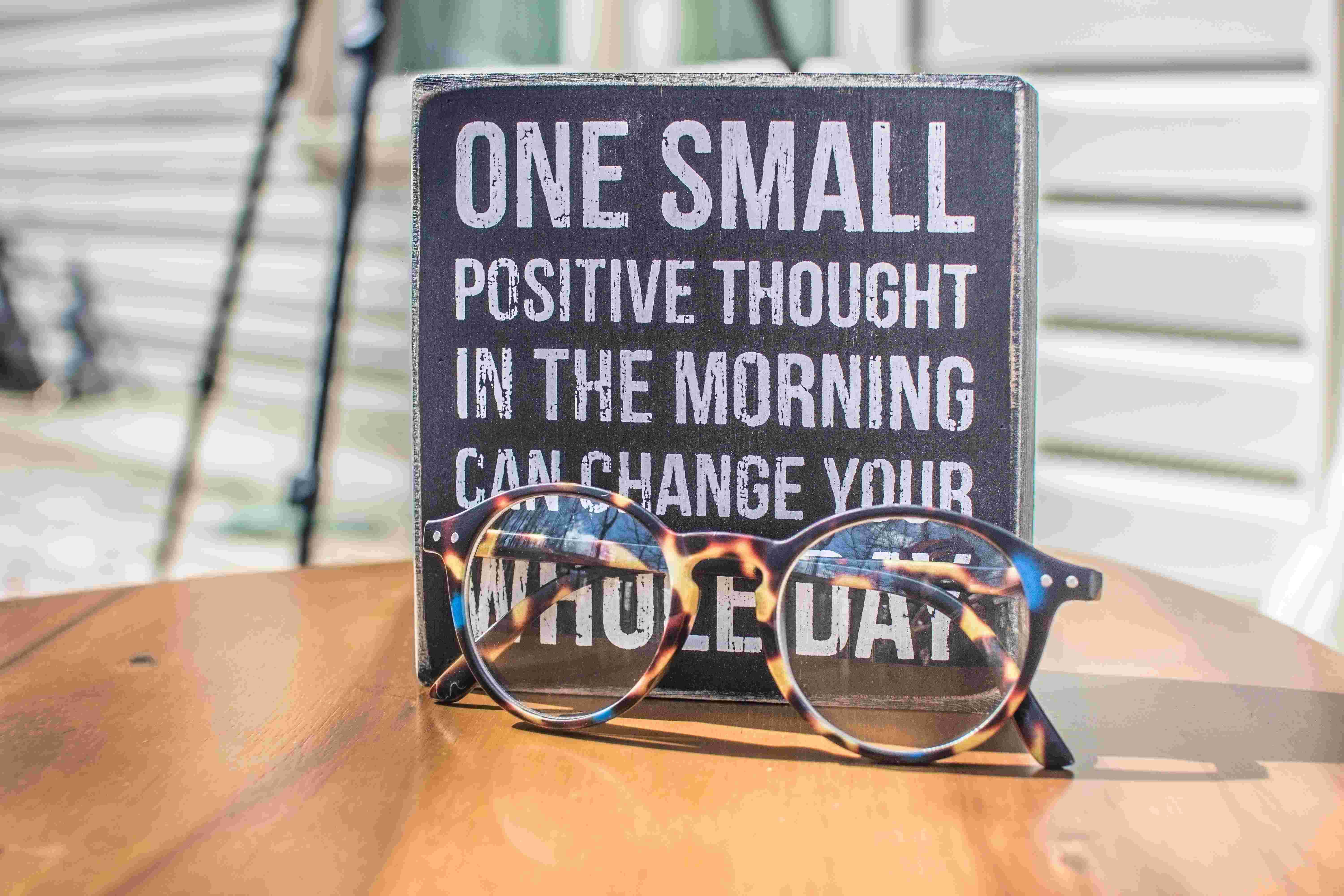"""quote on a black box behind sunglasses """"One small positive thought in the morning can change your whole day""""."""