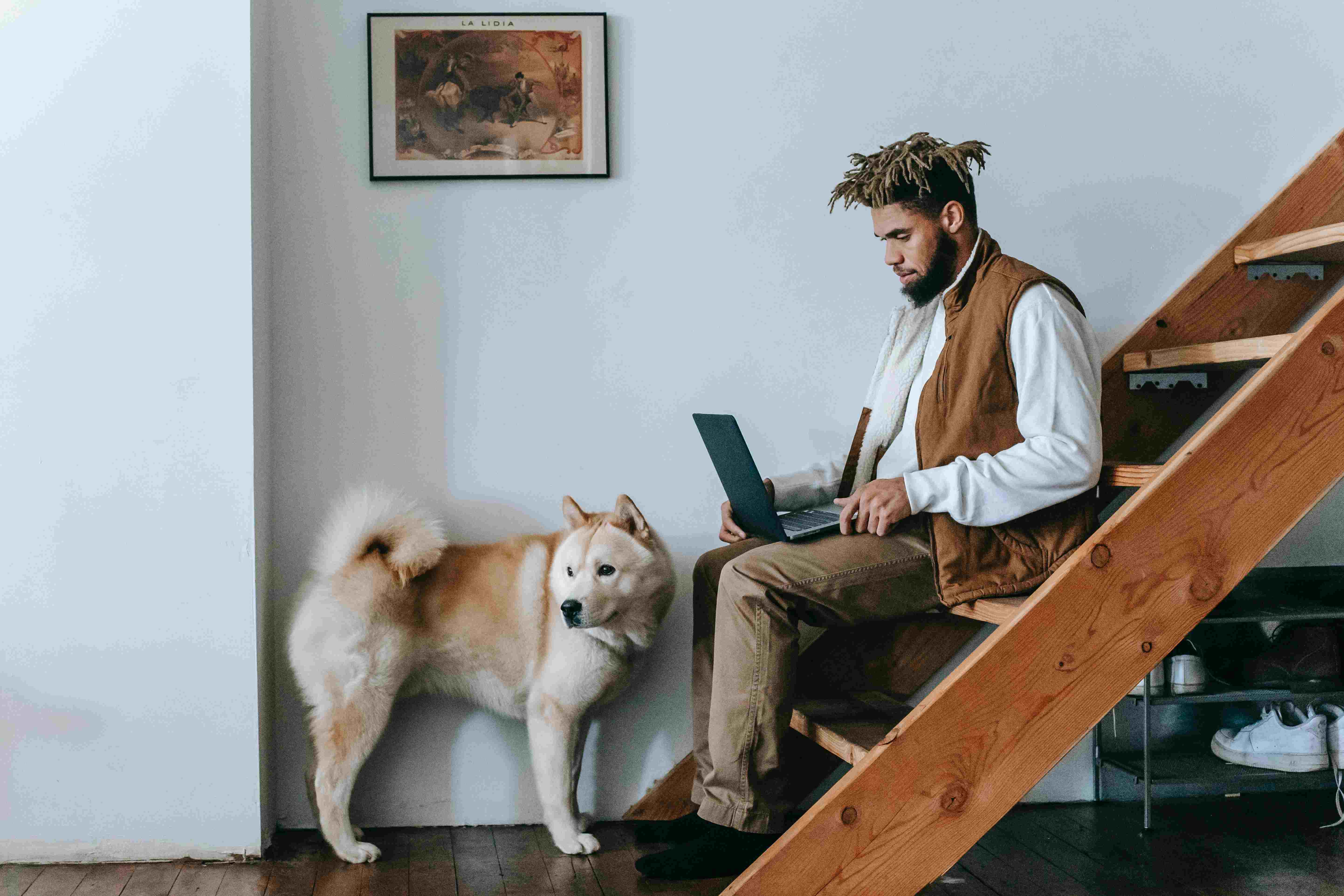 a man sitting on stairs with his dog