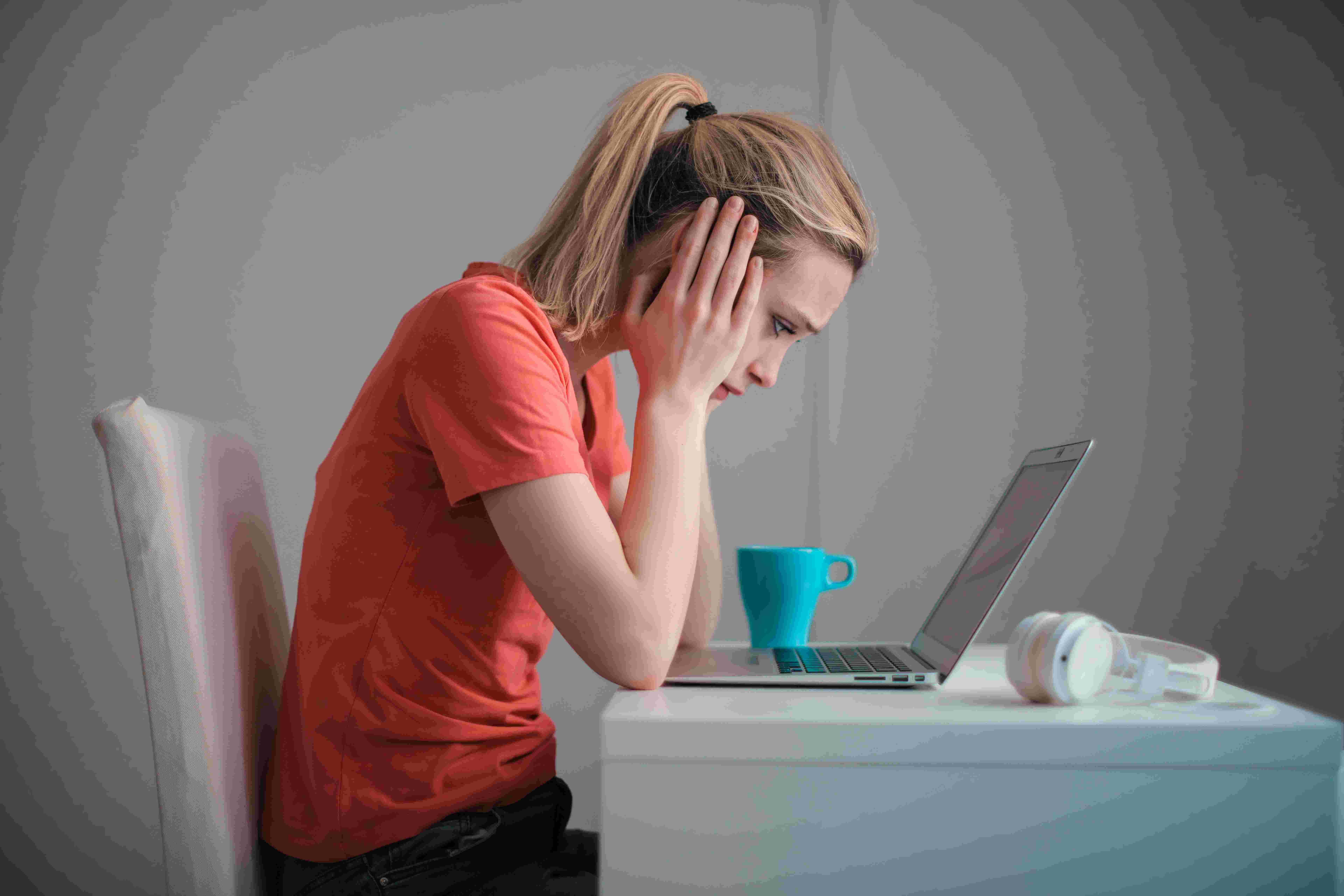 A girl in sad mood sitting in front of her laptop