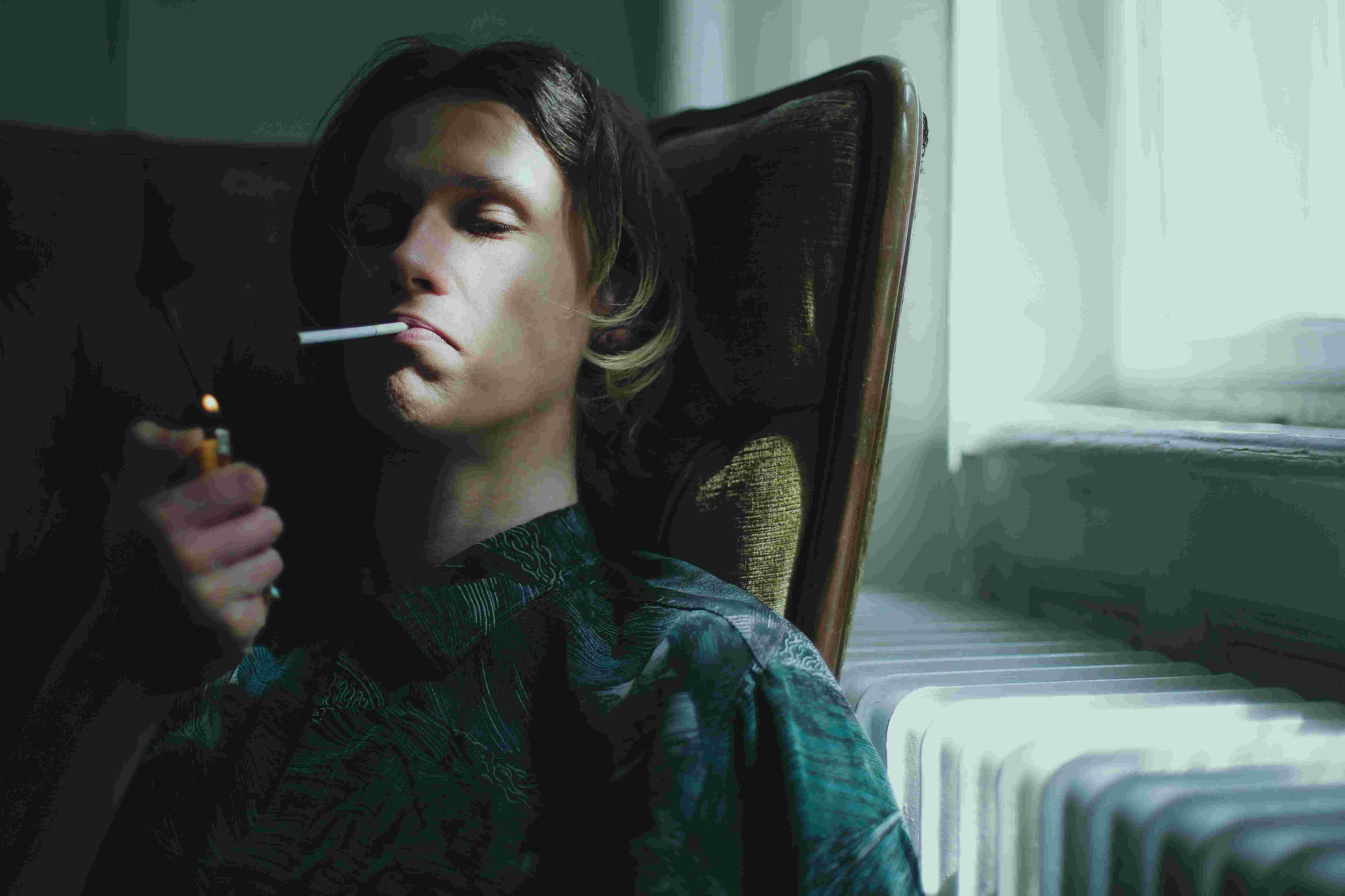 A boy, cigrette in his mouth and lighter in his hand preparing for smoking