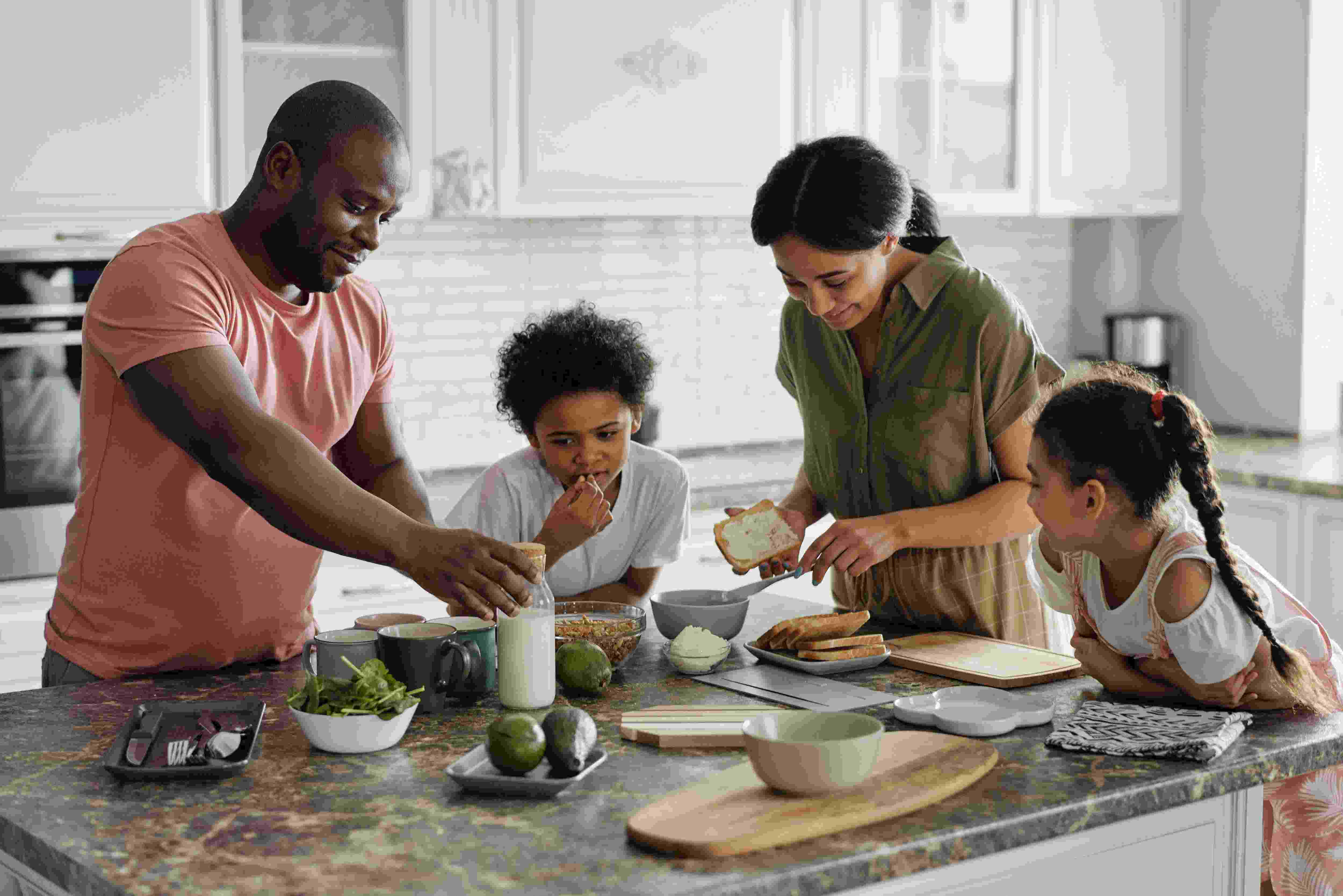 a black african -american family preparing dining table for dinner while their kid is stealing something