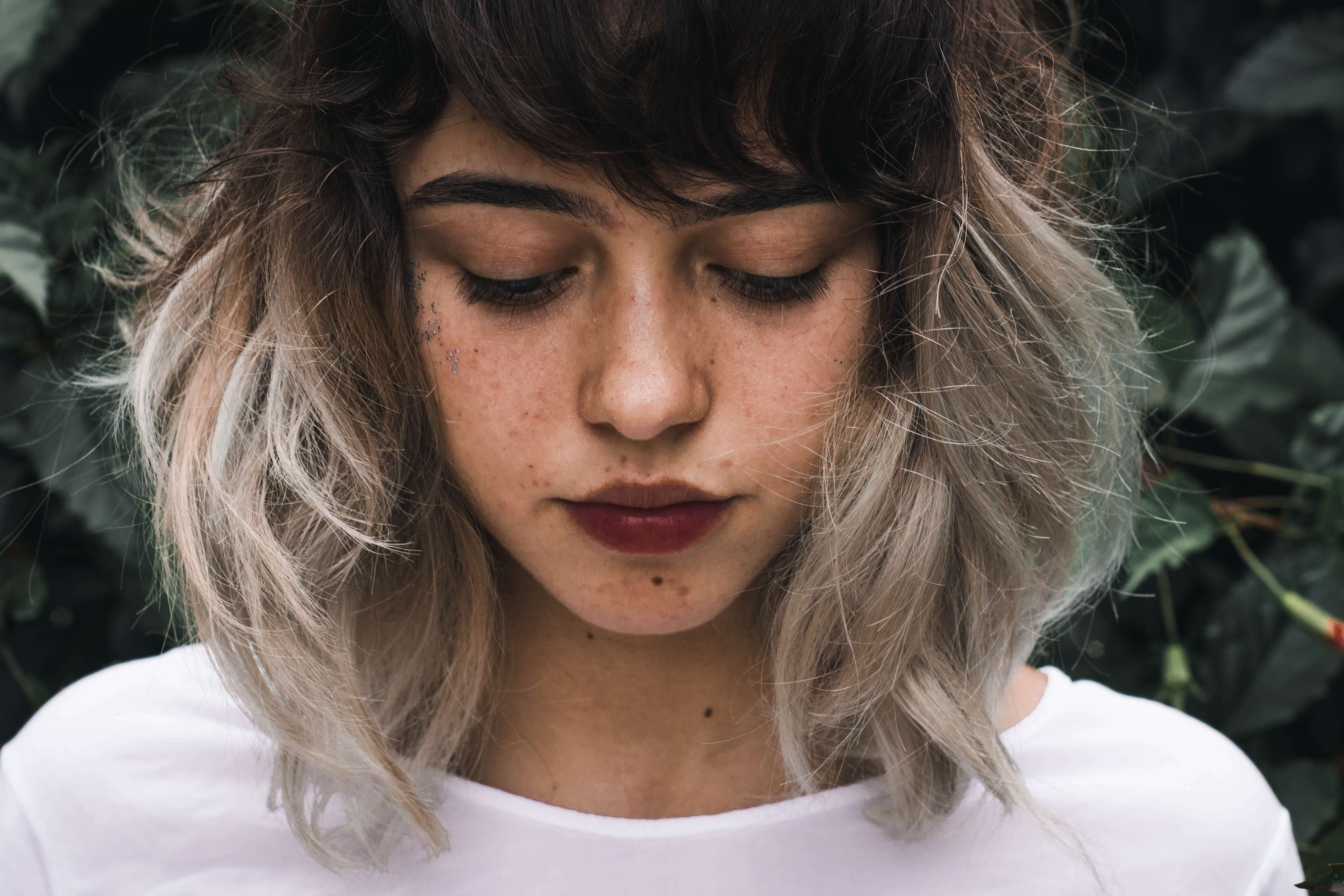 a girl with borderline personality disorder looking down with white and black beautiful hairs