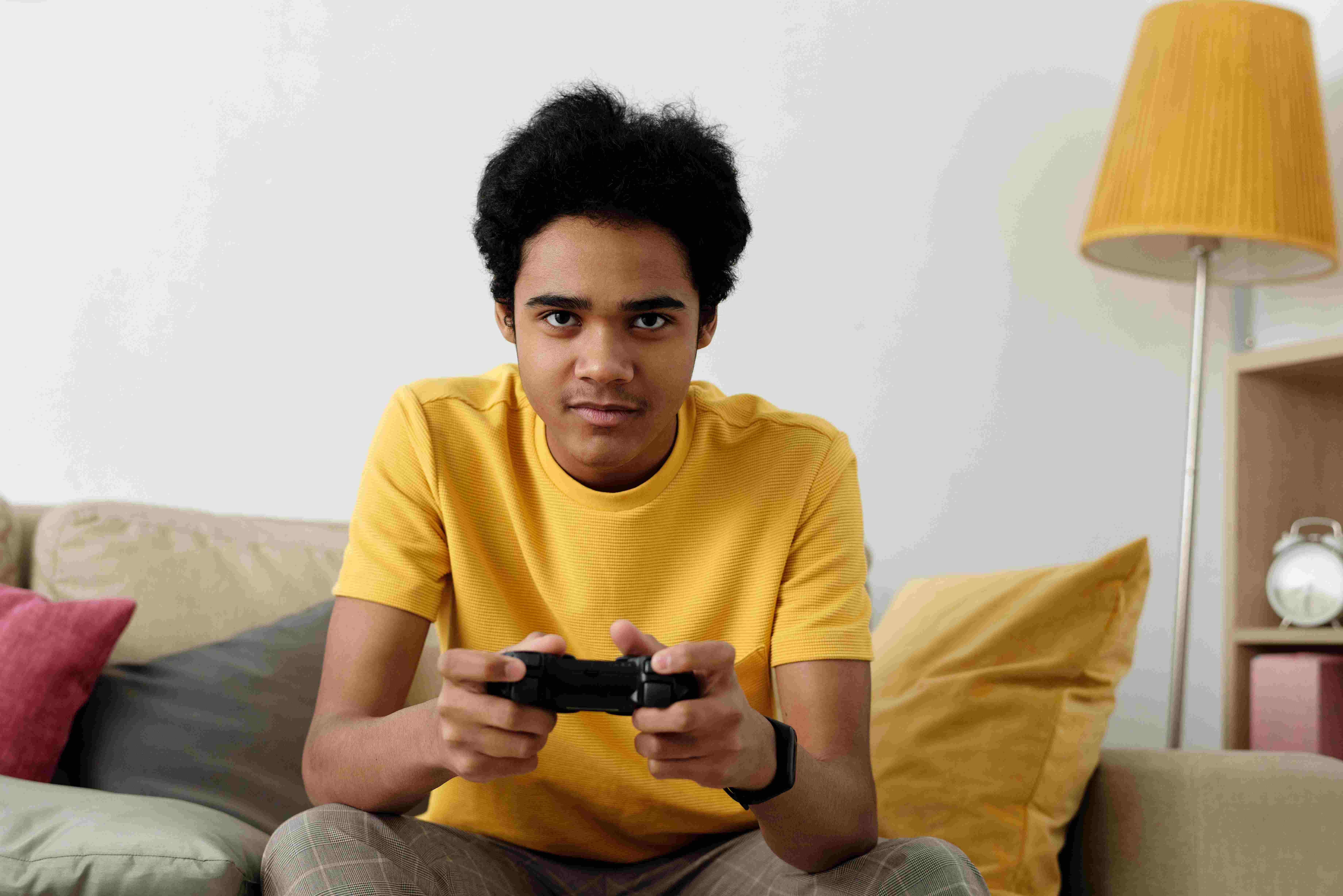 a boy in yellow t-shirt playing games extensively