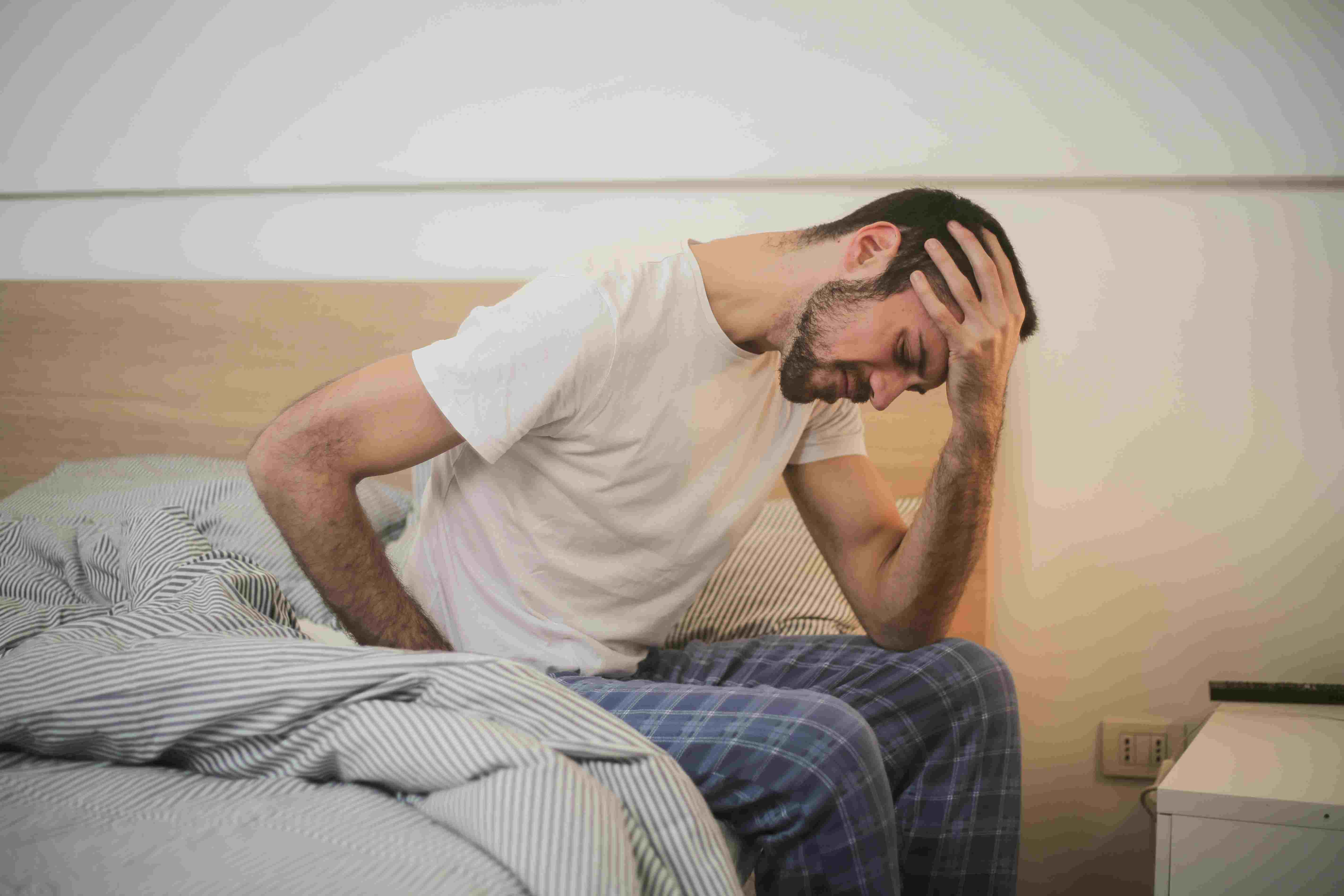 a man holding his head sitting on bed-  treatment for hypochondria