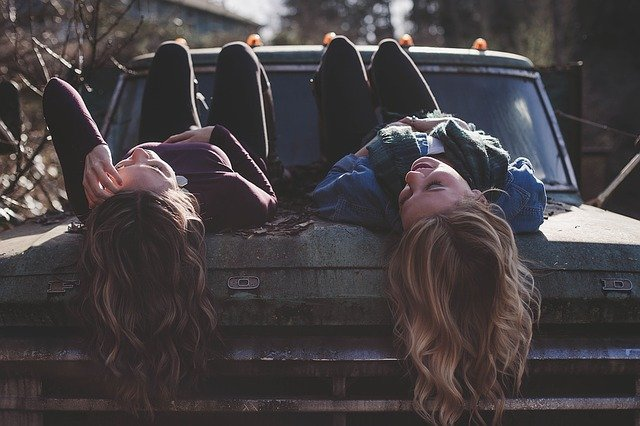two girls laying down a car