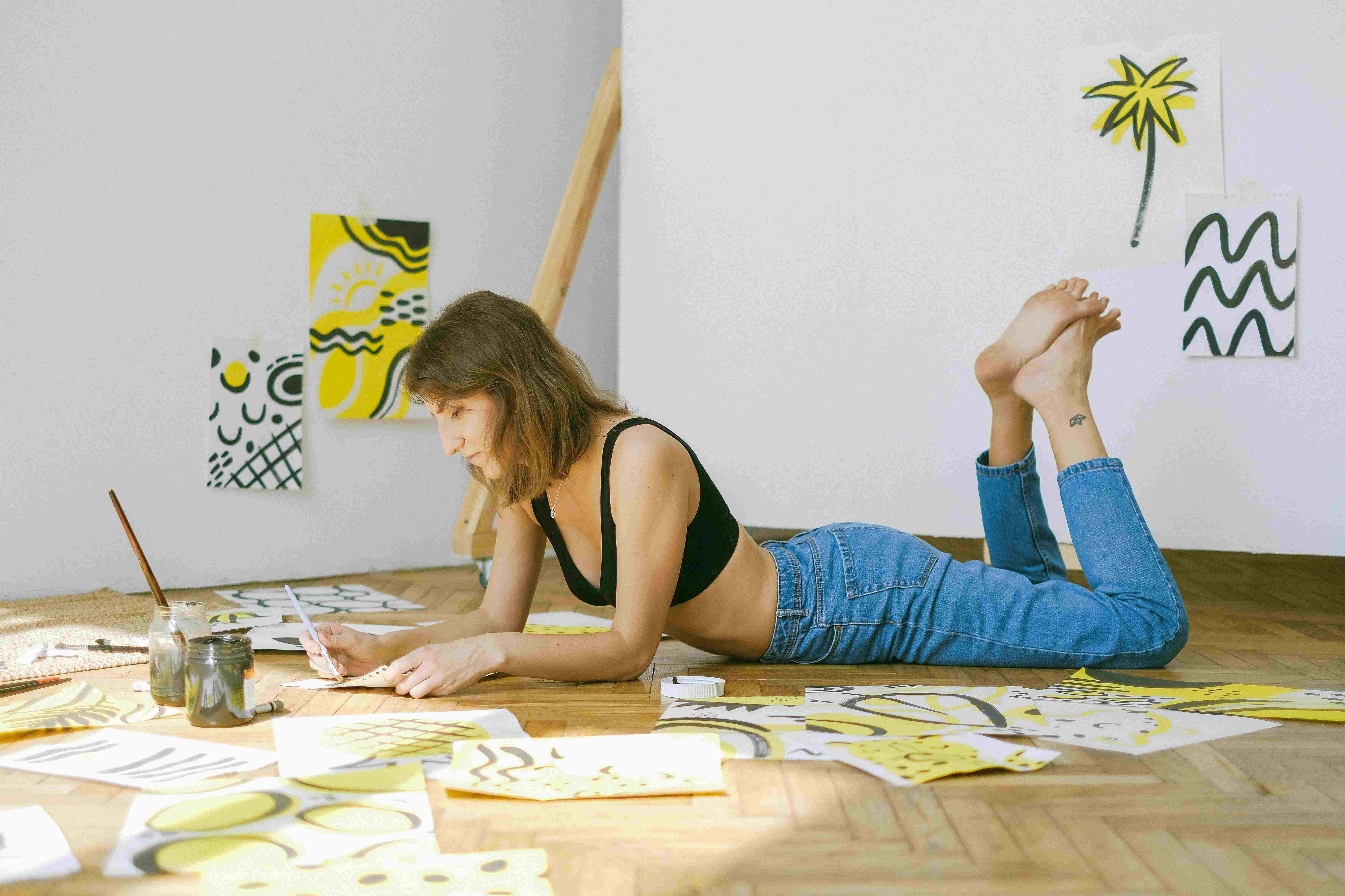 A women laying down on floor and drwaing beautiful art drawings